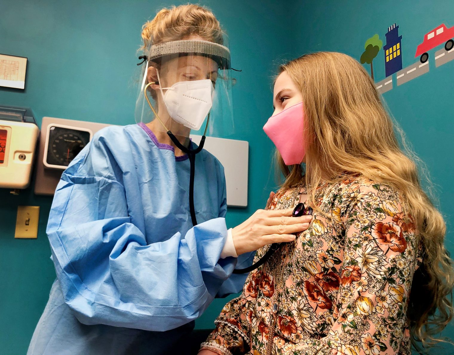 Mary Bailey, MD examines a patient with a stethoscope. She is wearing a face shield and the patient—a young girl—is wearing a mask.