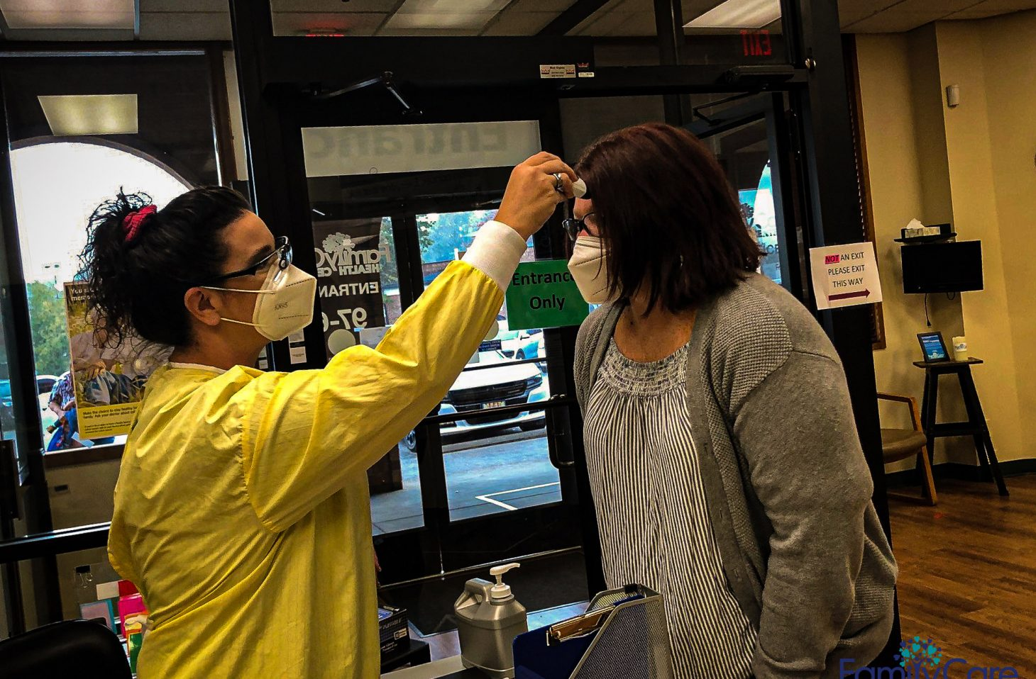 A nurse, wearing a face mask, takes the temperature of a patient, also wearing a face mask.