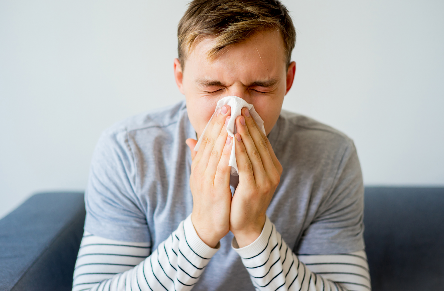 A young man is sneezing into a tissue.